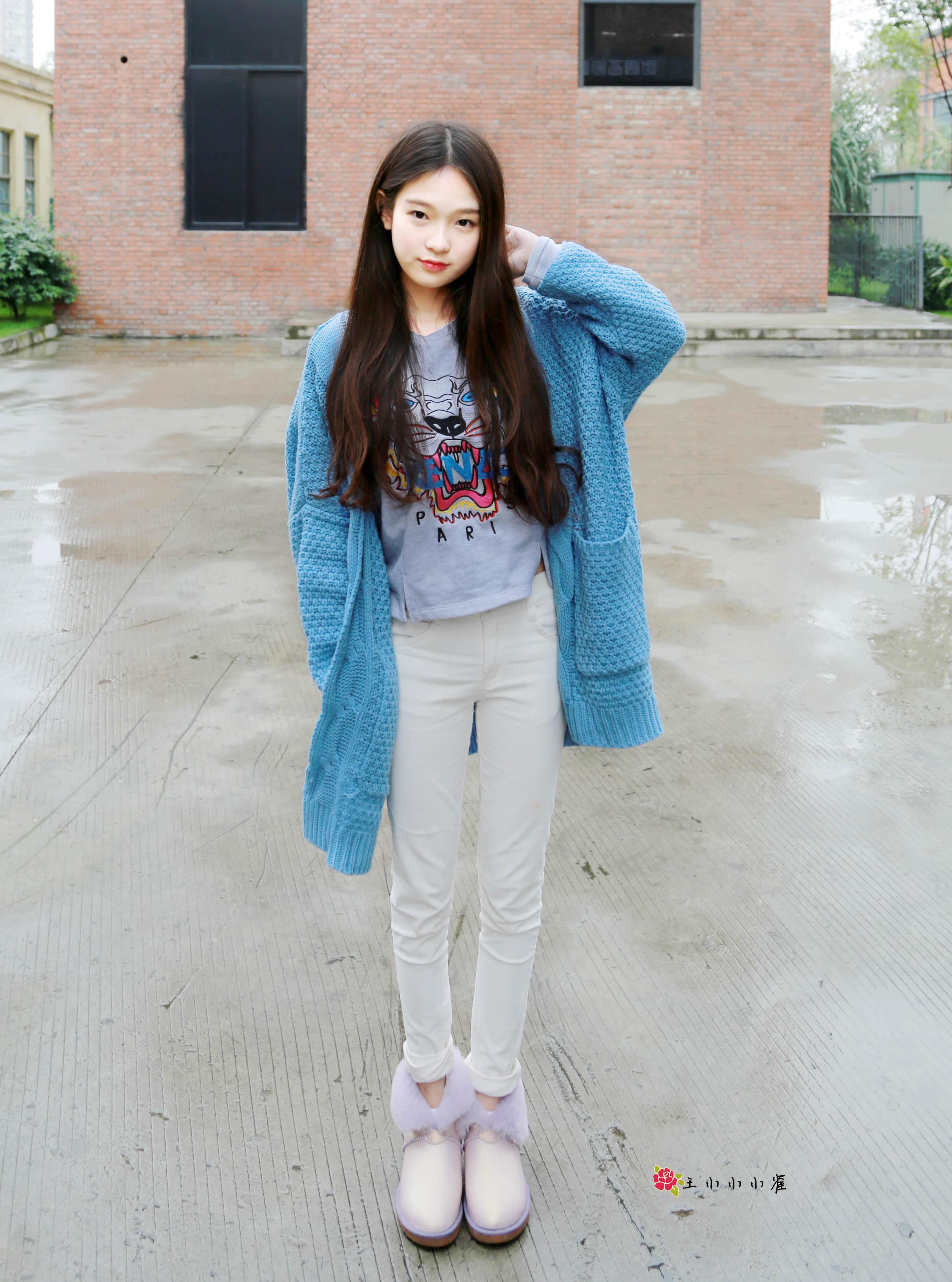 宽松的毛衣外套搭配灰色短款卫衣和白色的裤子