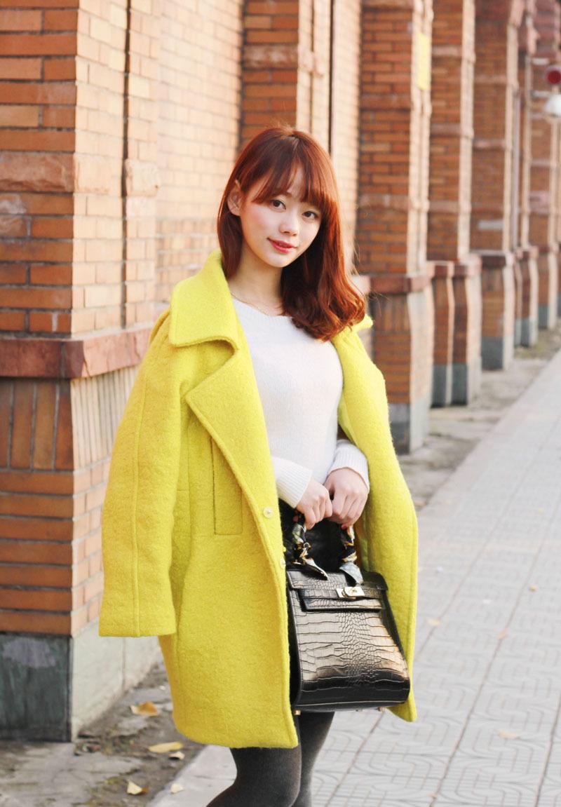 黄色呢子大衣搭配白色毛衣和黑色裙子